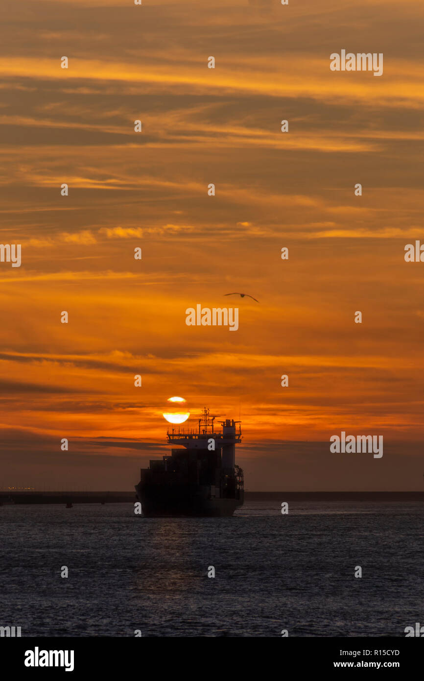Container vessel leaving the Rotterdam seaport toward the deep ocean under a vivid sunset, Amsterdam, Netherlands Stock Photo