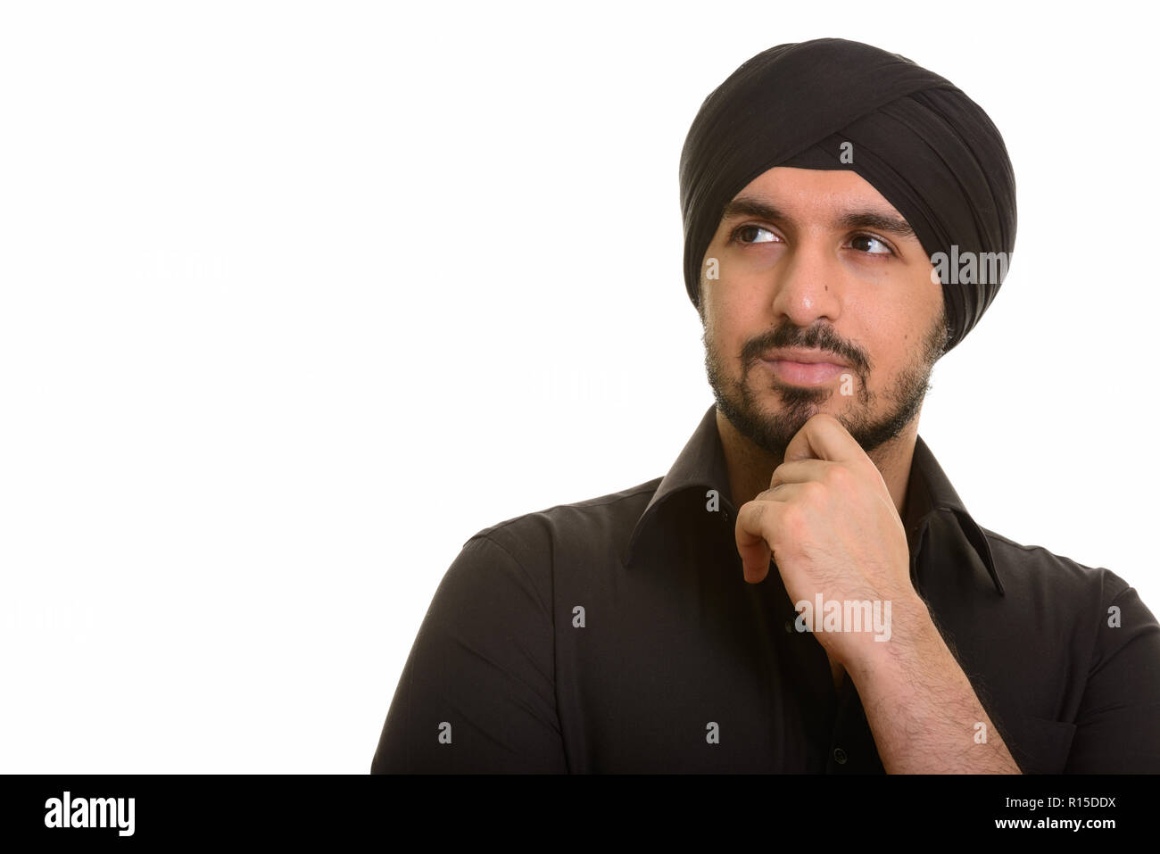 Portrait of young Indian Sikh man thinking - Stock Image