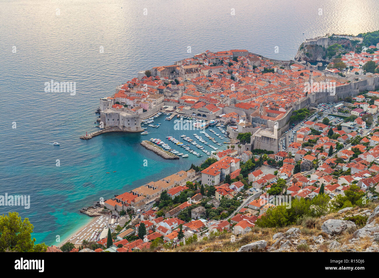 View from above to the intire old town Dubrovnik surrounded by its walls, the harbour full of boats and the beach with cristal clear tourquoise whater - Stock Image