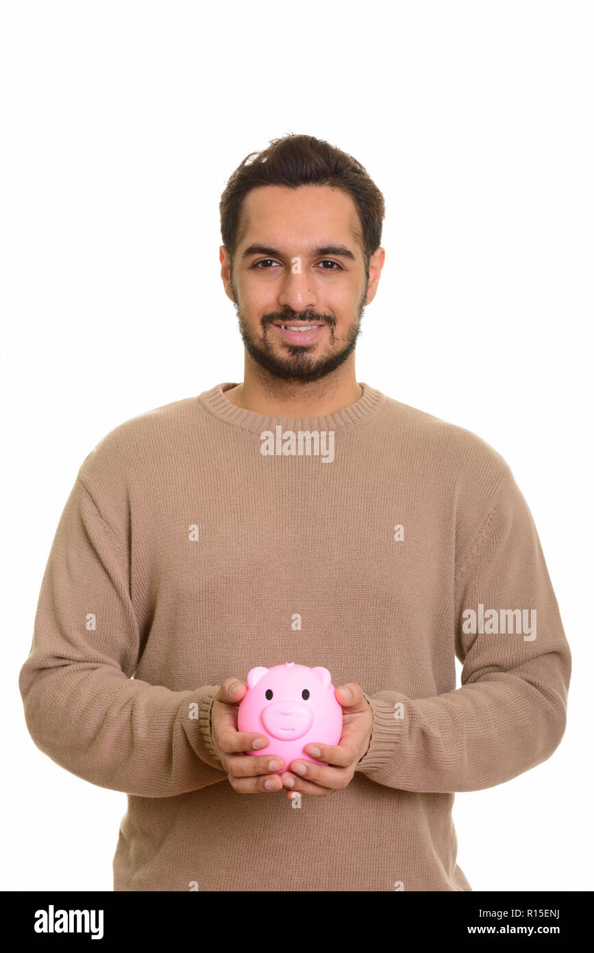 Young happy Indian man holding piggy bank Stock Photo