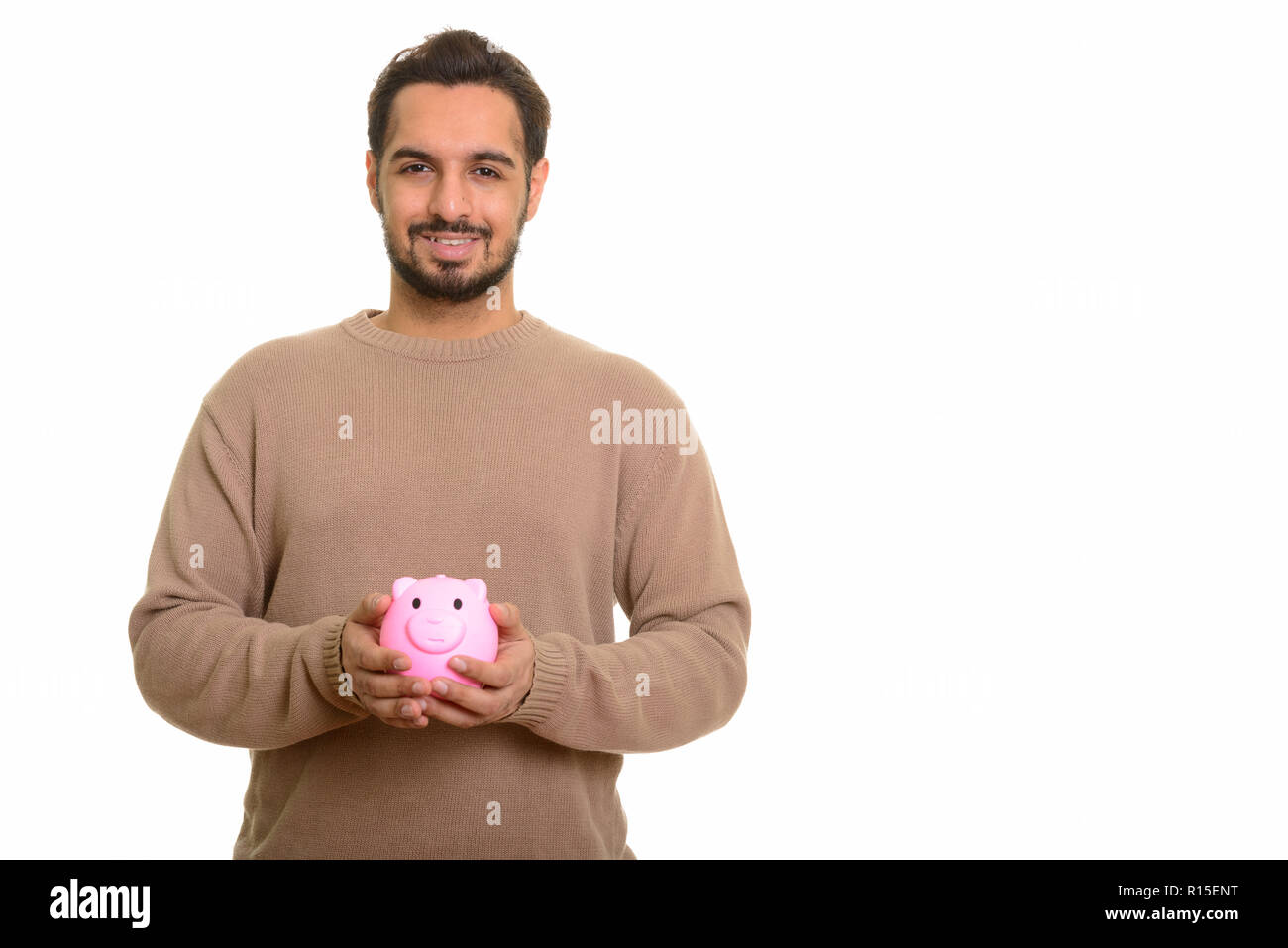 Young happy Indian man holding piggy bank - Stock Image