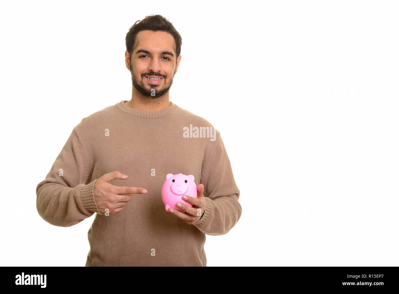 Young happy Indian man holding piggy bank and pointing finger - Stock Image