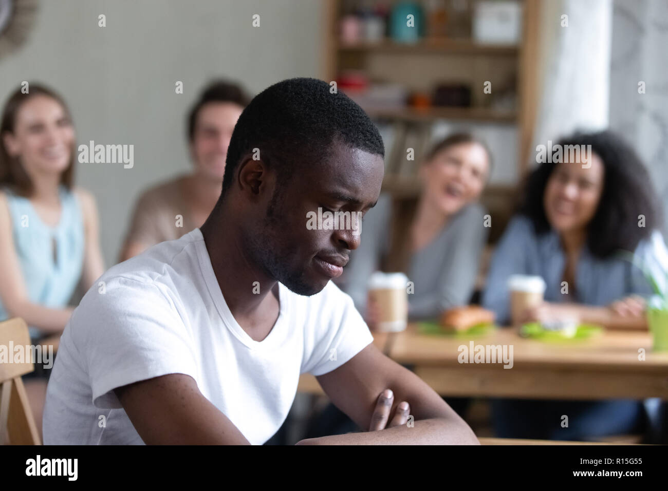 Group diverse people sitting in cafe laughing scoffing at black guy. Focus on sitting separately man feels upset and unhappy, schoolmates not take him - Stock Image