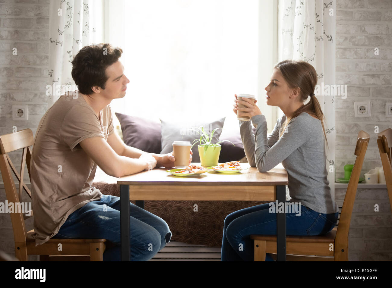 Serious attractive girlfriend spends time in cafe with boyfriend sitting together at table chatting discussing, side view. Millennial guy looking at g - Stock Image