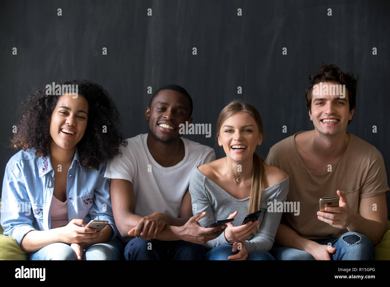 Happy diverse students multiracial friends sitting together indoor. Attractive smiling girls handsome guys holding mobile phones laughing looking at c - Stock Image