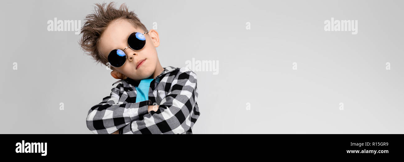 192026e5b A handsome boy in a plaid shirt, blue shirt and jeans stands on a gray  background. The boy is wearing round glasses. Red-haired boy folded his  arms over his ...