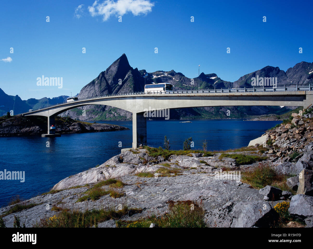 Norway, Lofotens, Moskenesoya, Bridge linking the villages of Reine and Hamnoy with two buses crossing and Mt. Olstinden 675 metres in background. - Stock Image