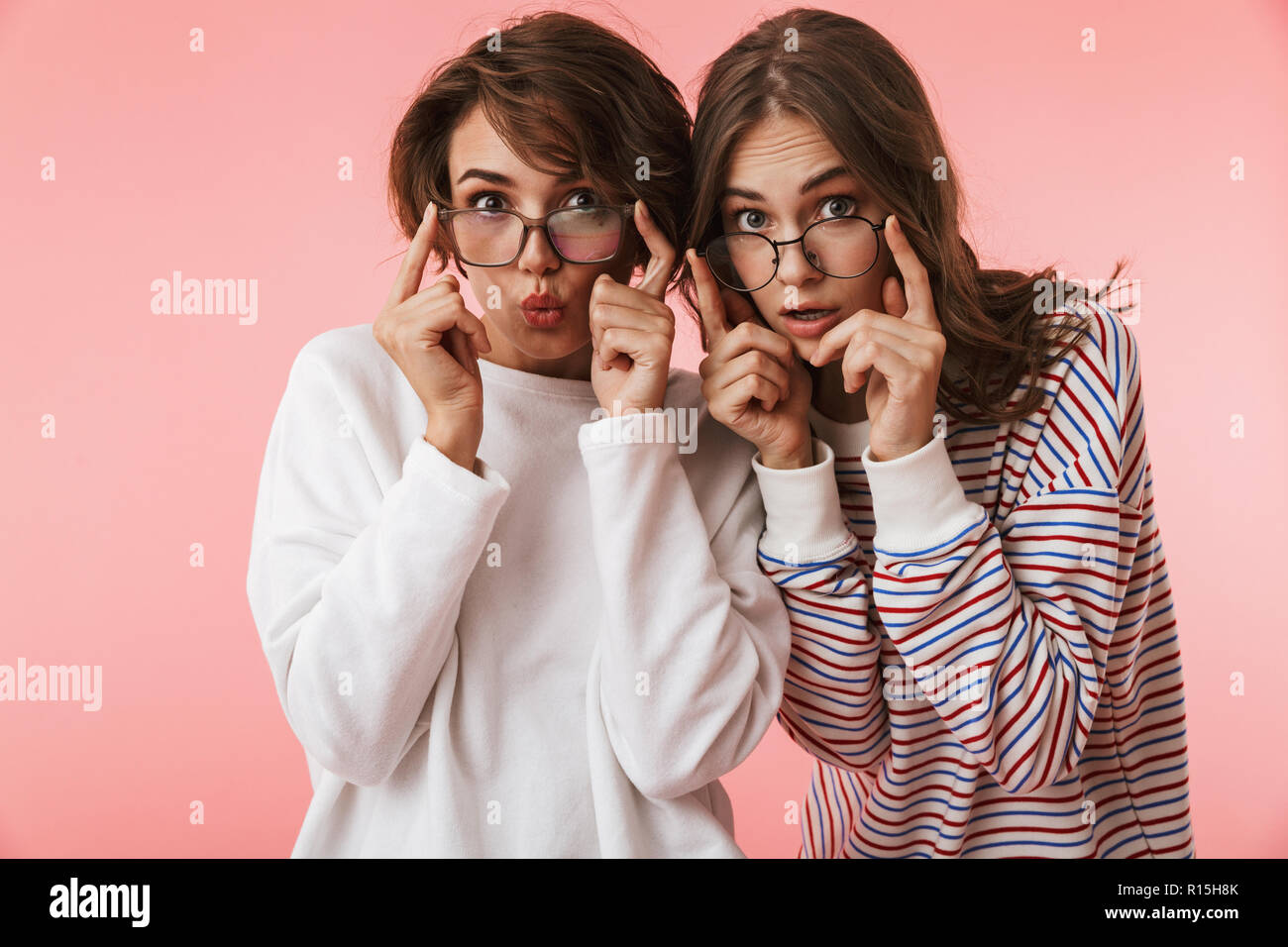 b6abe05339 Image of shocked emotional young women friends posing isolated over pink  background. - Stock Image