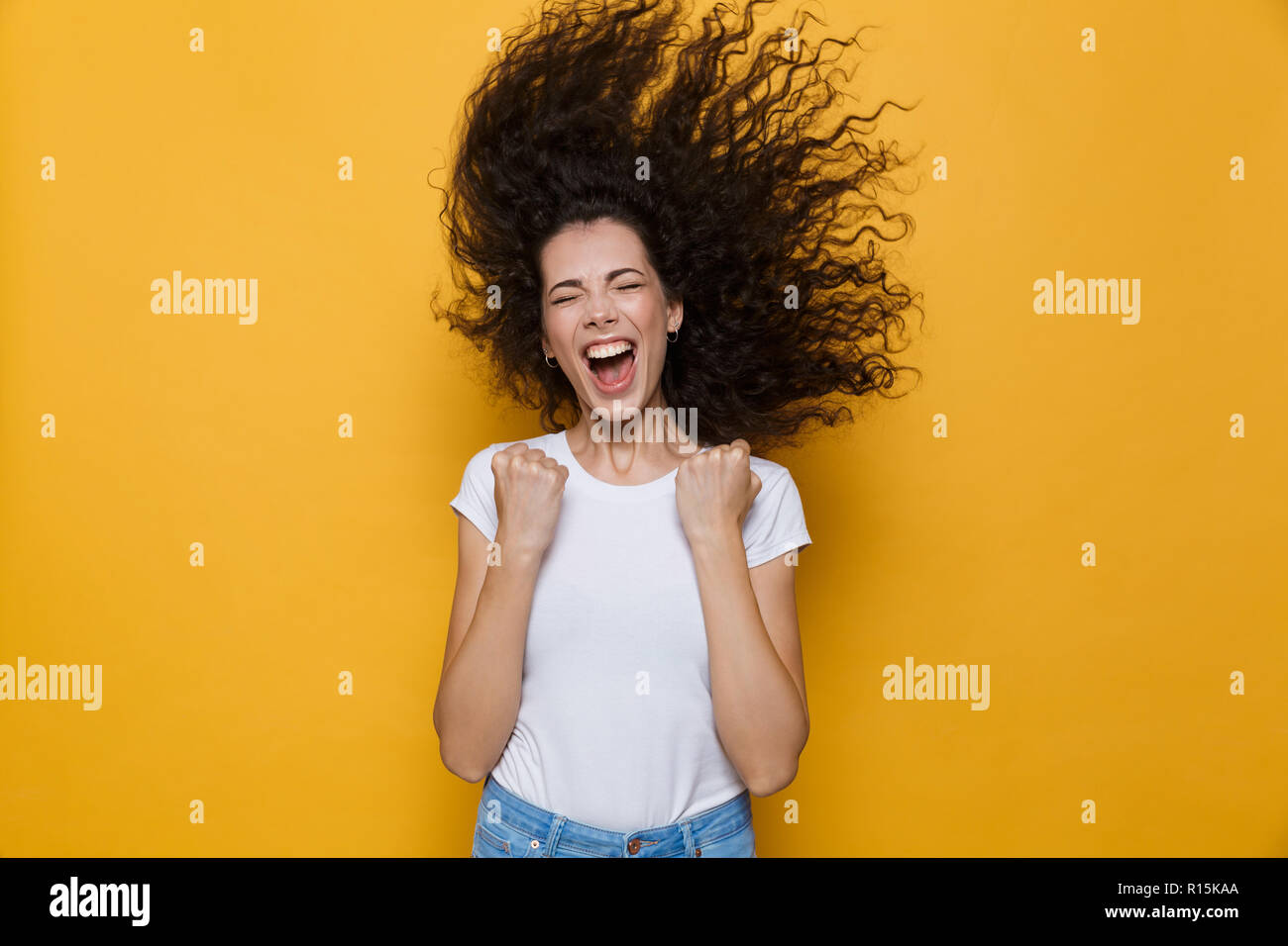 Image of excited woman with shaking hair screaming and rejoicing isolated over yellow background - Stock Image