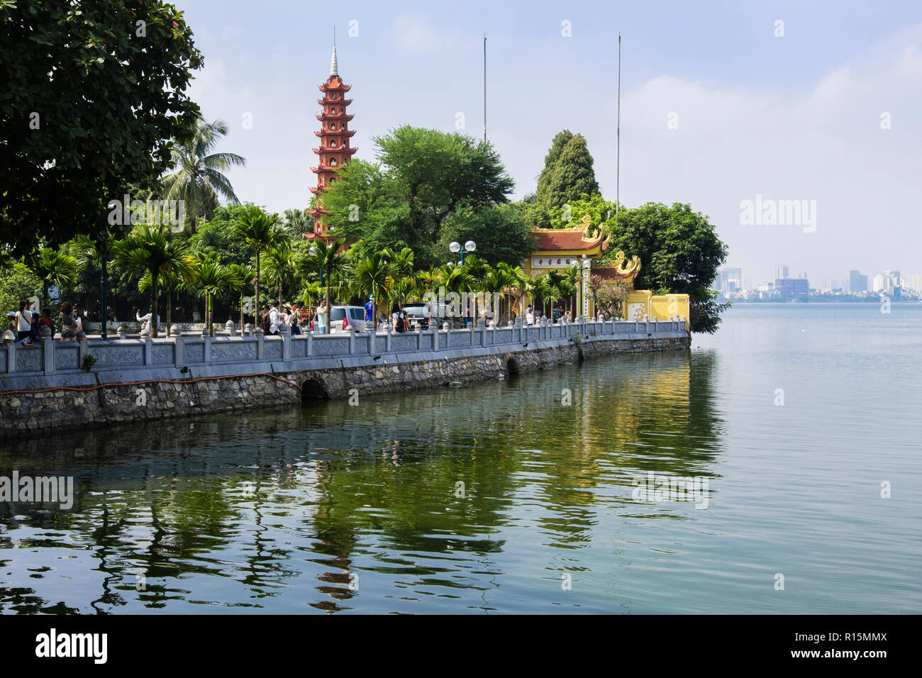 Tourists on causeway leading to Tran Quoc Pagoda and temple on West Lake. Hanoi, Vietnam, Asia - Stock Image