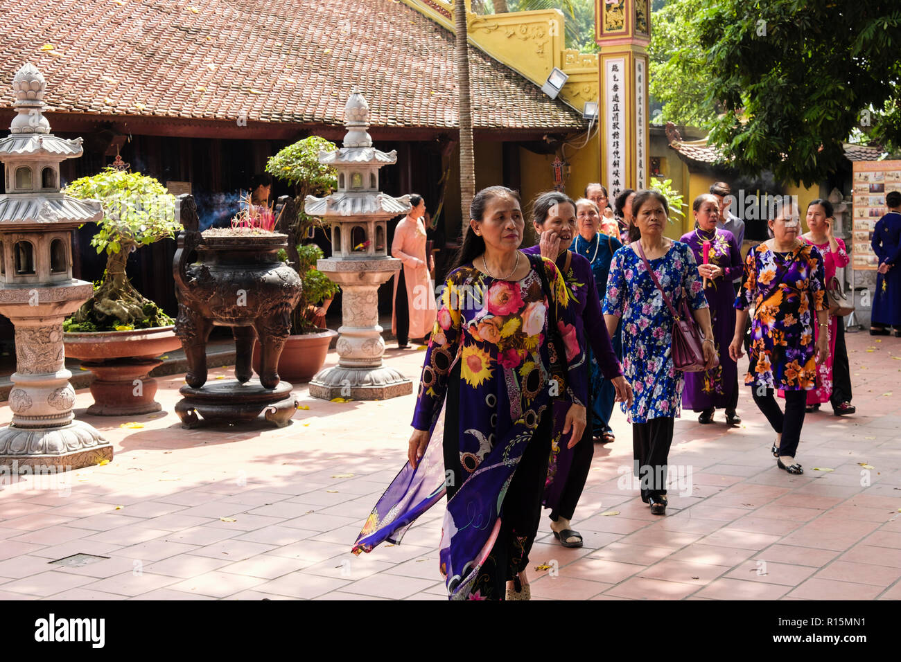 Asian women in tradional dress visiting Tran Quoc temple. Hanoi, Vietnam, Asia - Stock Image