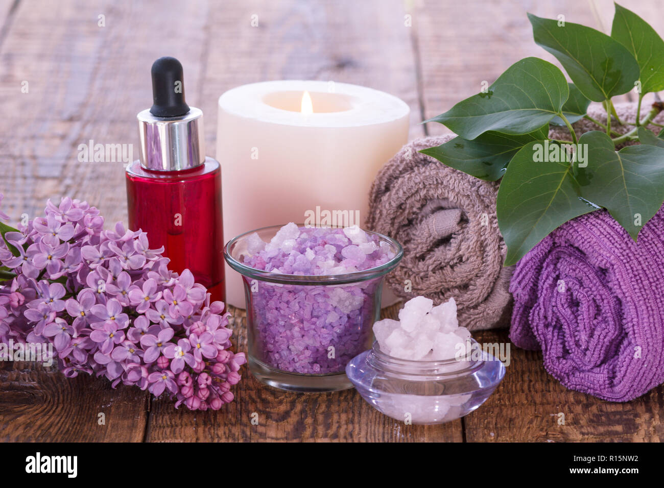 Lilac flowers, red bottle with aromatic oil, burning candle
