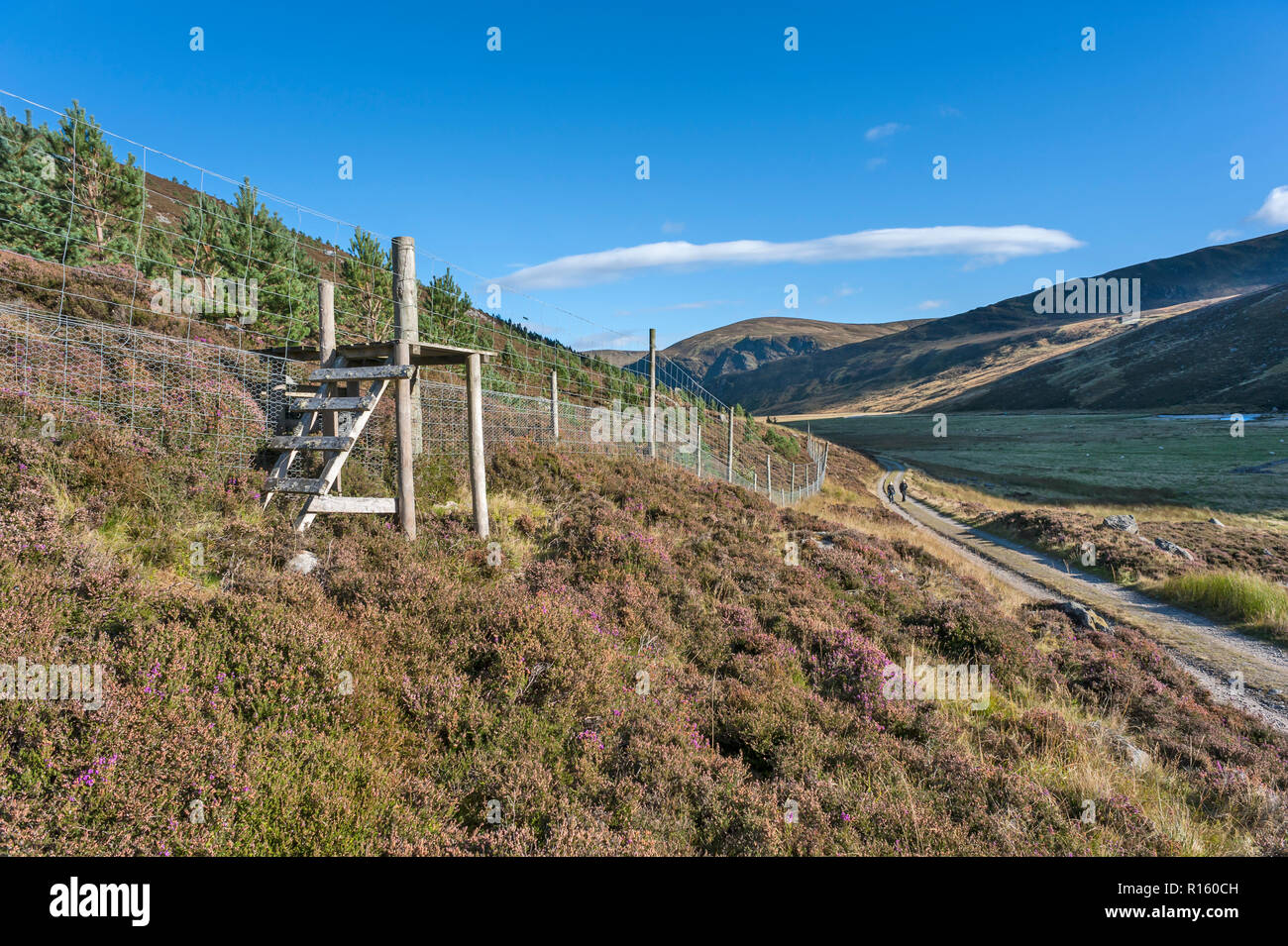 A stile over deer fence in Glen Esk with two female walkers hiking along path  in background - Stock Image