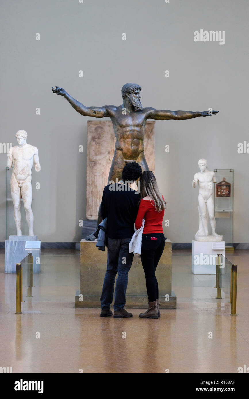Athens. Greece. Visitors at the National Archaeological Museum of Athens looking at the Artemision Bronze, statue representing Poseidon or Zeus, ancie - Stock Image