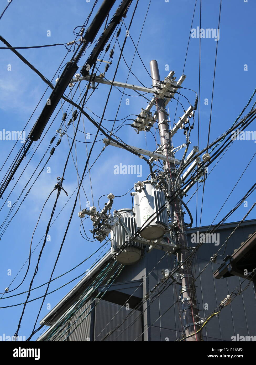 Street scene with a mass of tangled wires and cables at the top of an electricity pylon, Kyoto, Japan; underground cabling is not common. - Stock Image
