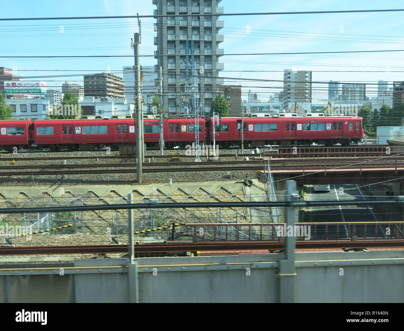 View of a red train on another line as we approach Nagoya station, central Japan - Stock Image