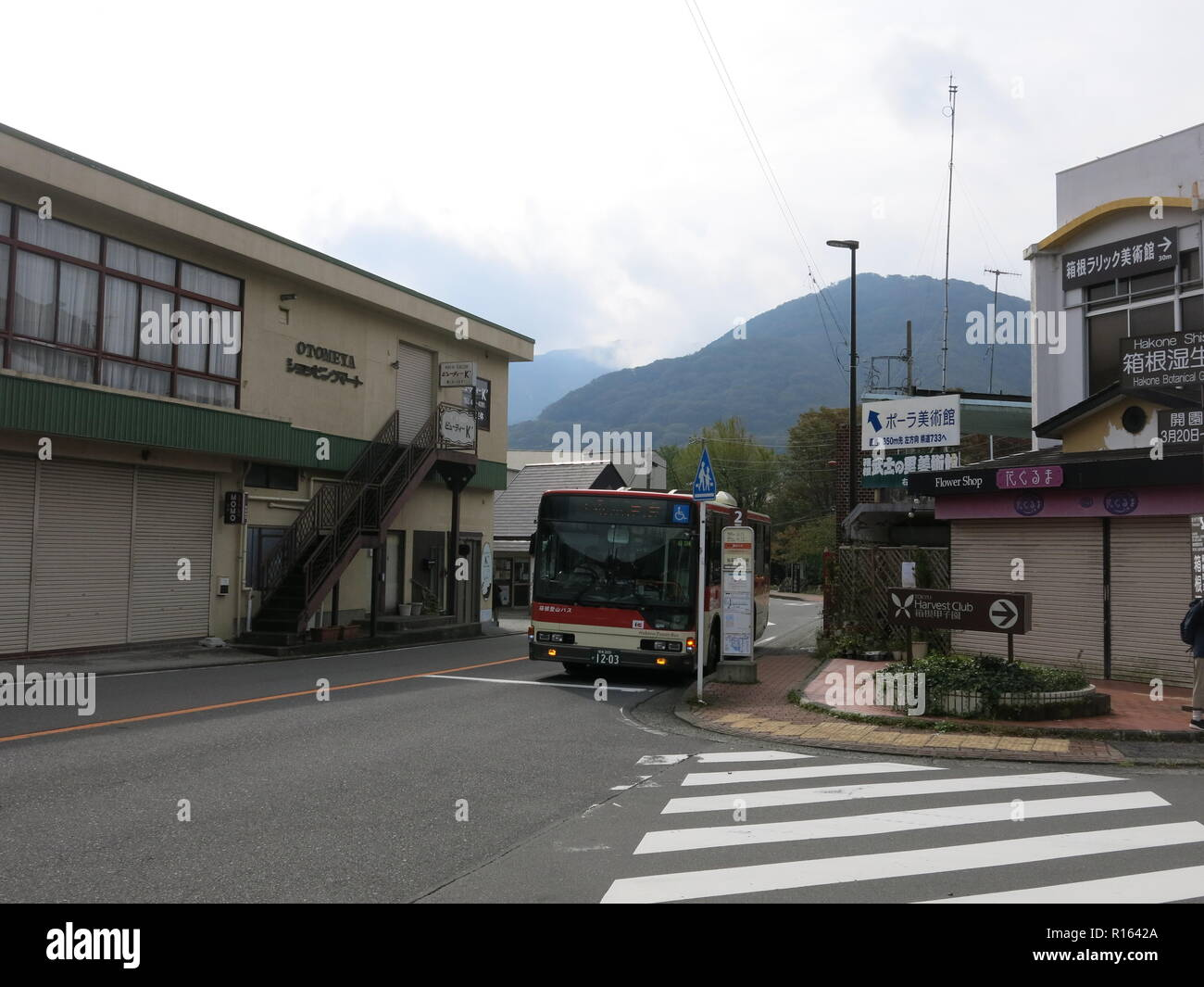 Street scene with a pedestrian crossing and bus standing at bus-stop number 2 in Hakone-machi, Kanagawa Prefecture, rural Japan. - Stock Image