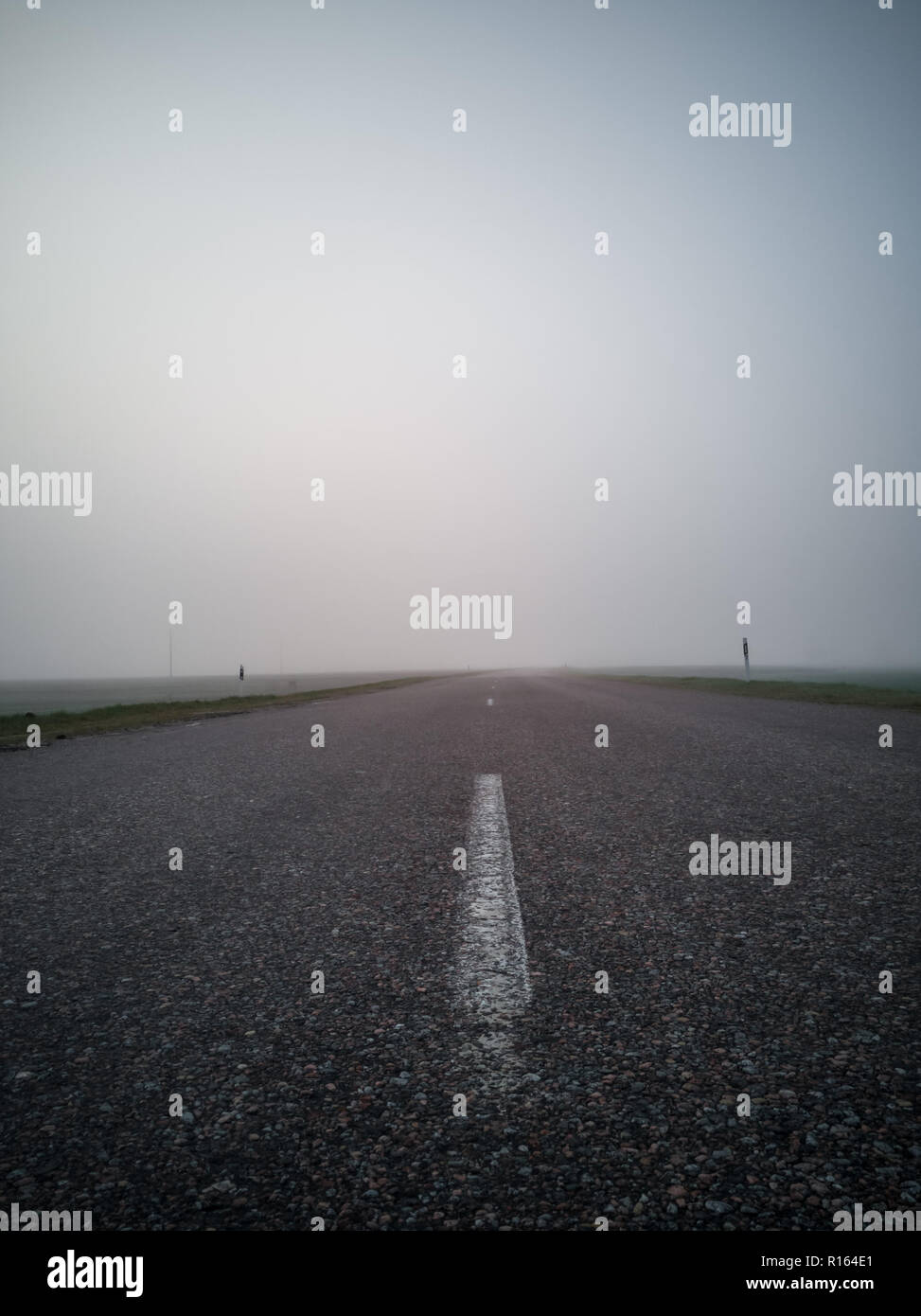 Blurred Road in an Early Morning  with a Heavy Mist Covering the Background and a Sun Shining Through Mist. Moody Photo with a Text Space - Stock Image