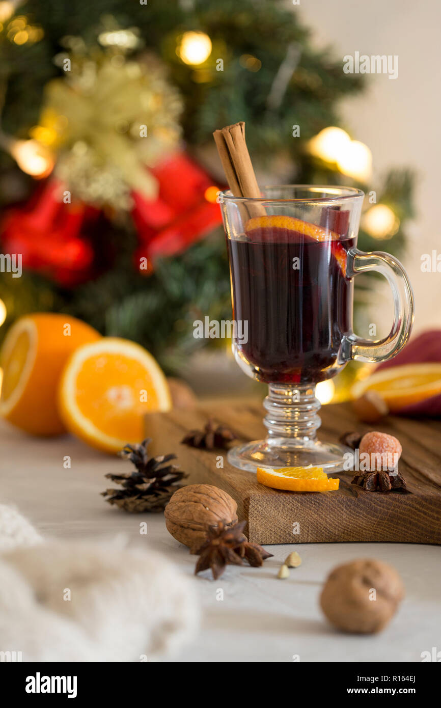 Winter composition. Mulled wine in glass on wood board at white background. Fir wreath, bells, tinsel and garlands, napkin, orange, cinnamon and spice Stock Photo