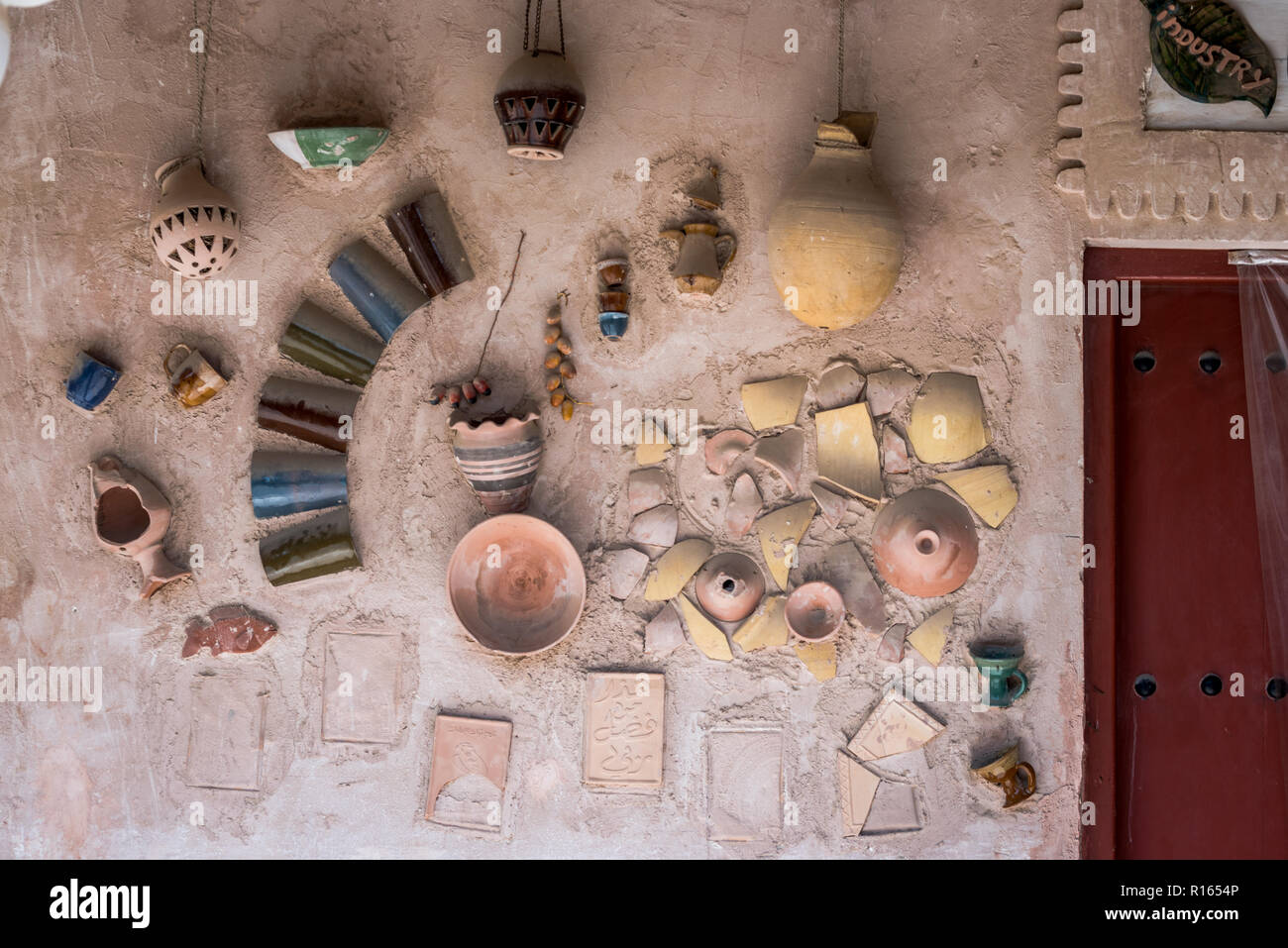 Old hand crafted pottery arranged and installed on the wall at Heritage village Abu Dhabi, UAE - Stock Image
