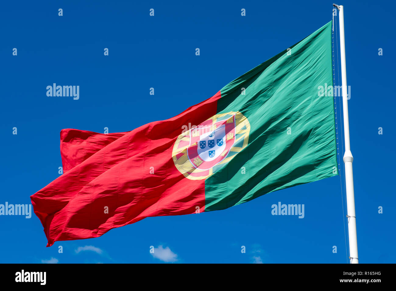 National flag of Portugal on a flagpole in front of blue sky. - Stock Image