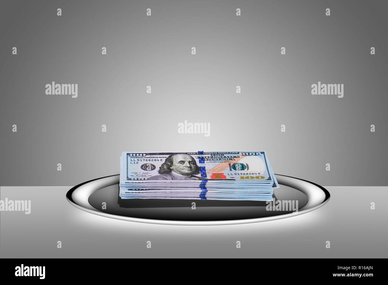 Stacked 100 dollar bills on silver platter - 'hand to on a silver platter' - Stock Image