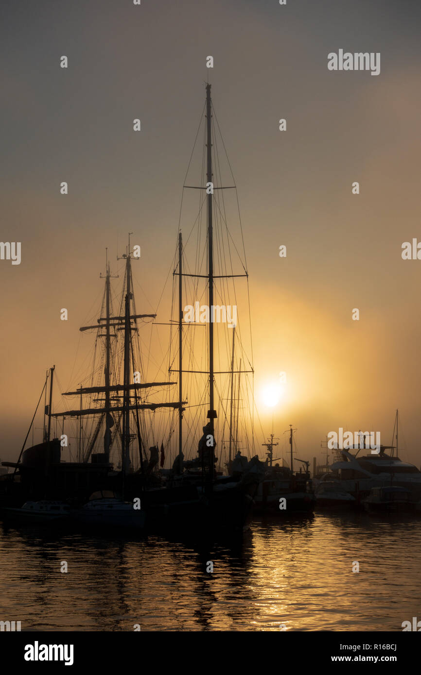 Ships silhouetted against dawn sky in Poole Stock Photo