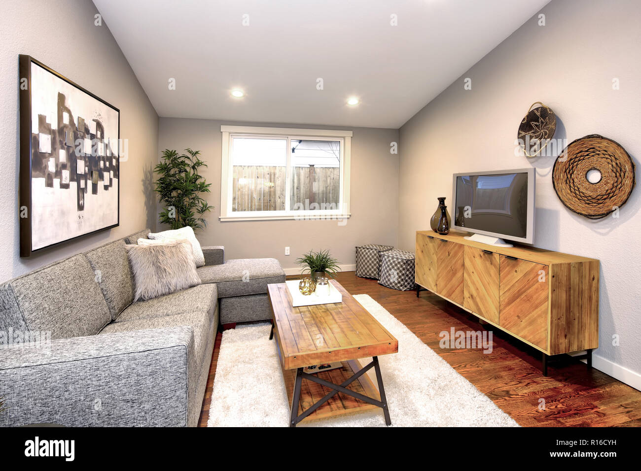 Living room in neutral colors with large gray sofa atop ...