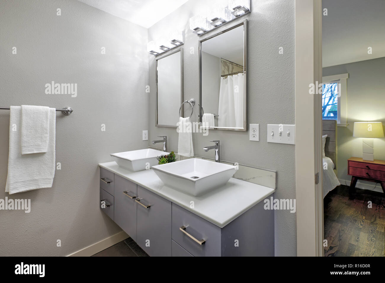 Luxurious Master Bathroom With Blue Vanity Cabinet And Two Square