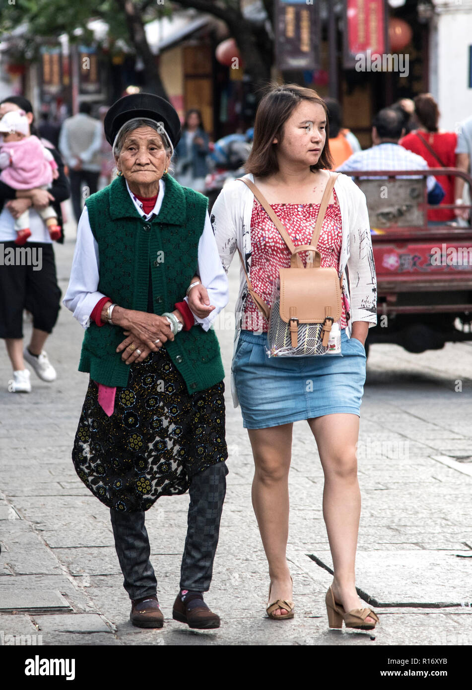 Old Chinese lady walking with young Chinese grand daughter in shopping district of Dali South West China. - Stock Image