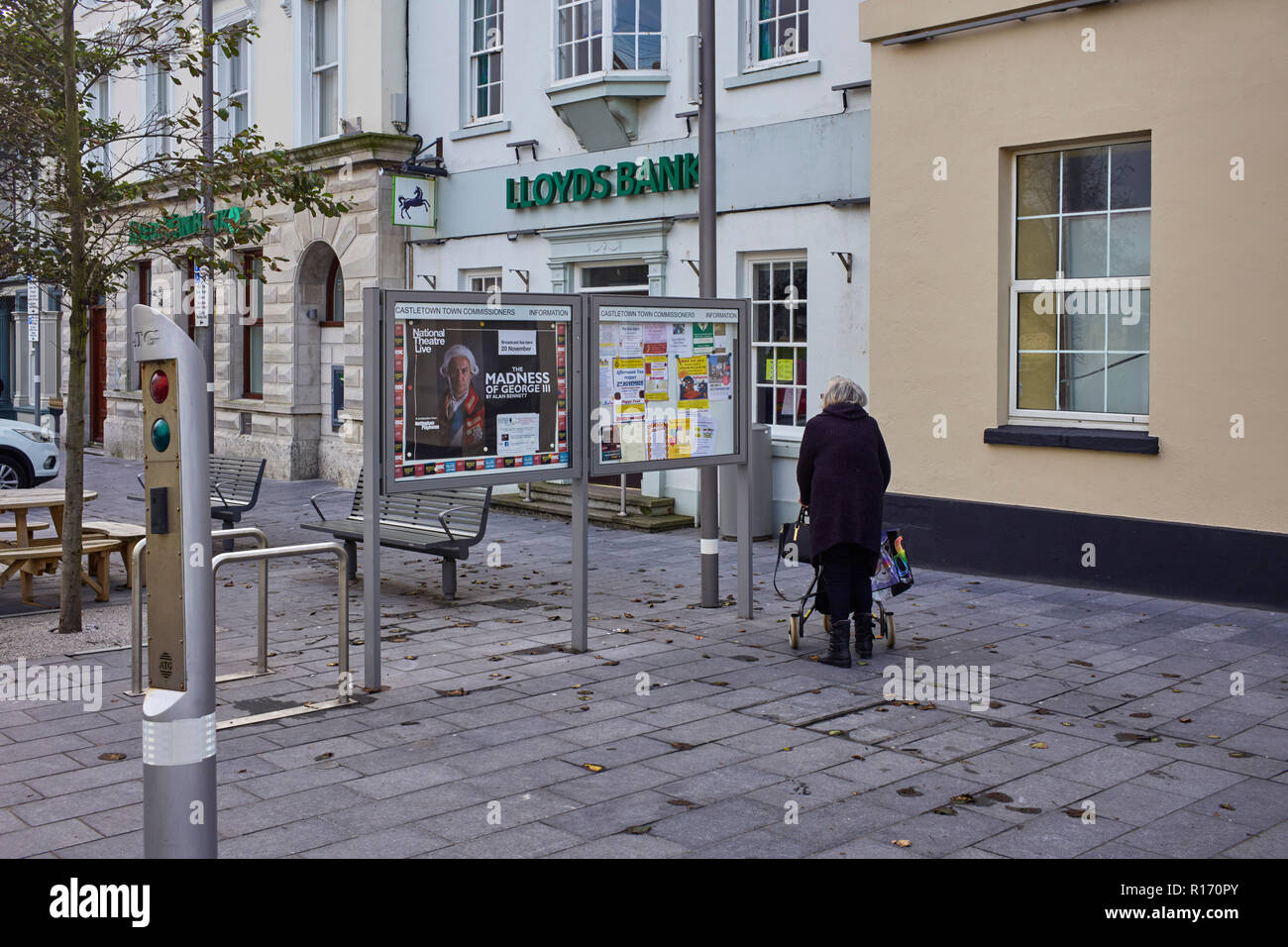 Older woman using a walker passes the town notice board at Castletown, Isle of Man - Stock Image