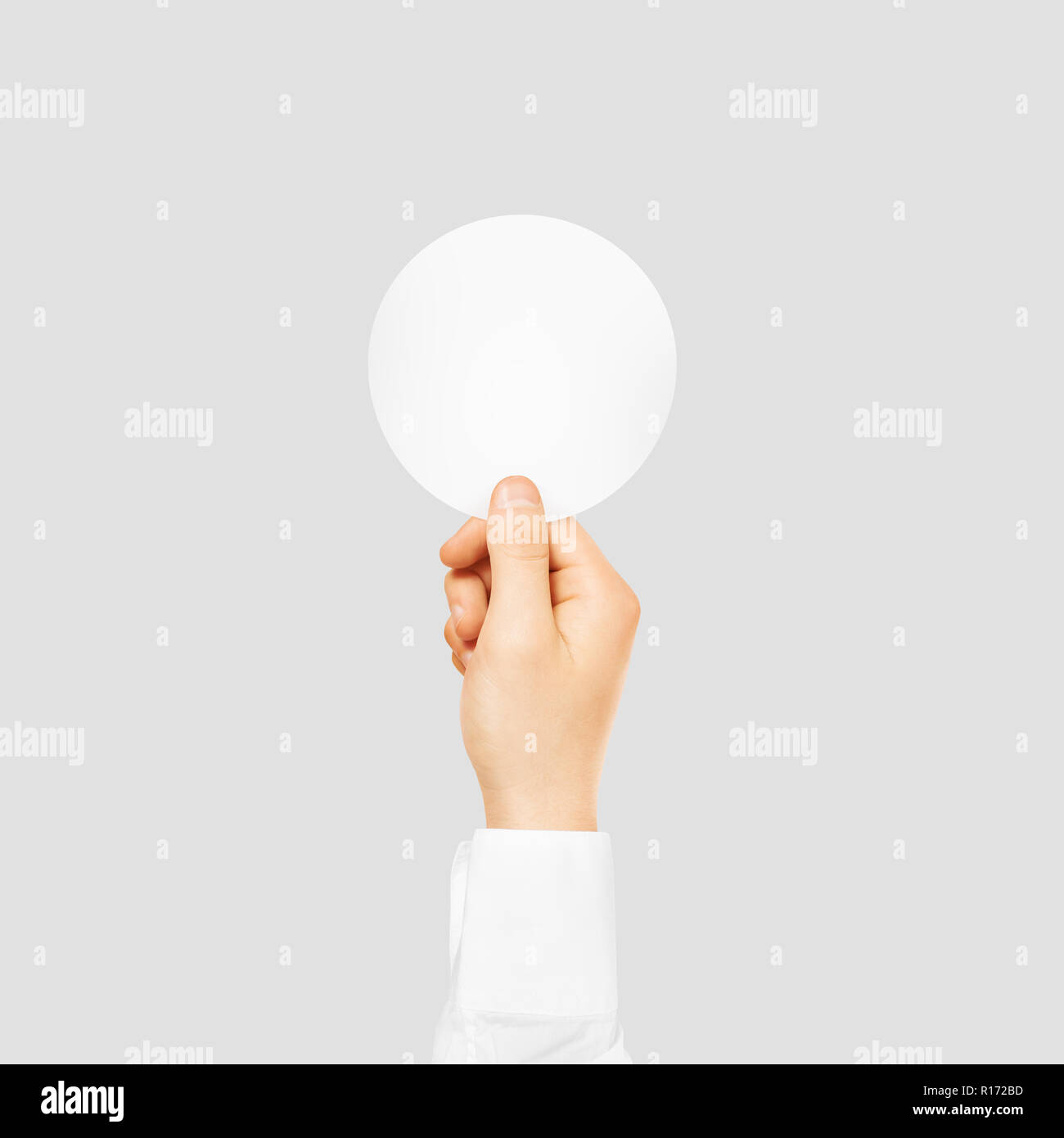 Hand holding round blank white sticker mock up isolated on gray