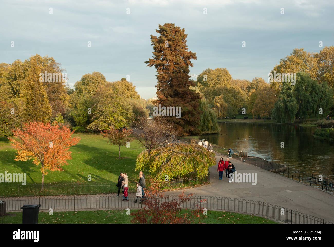 Historic St James's Park in the afternoon sunshine with autumnal colours. People walking in the distance by the lake. Stock Photo