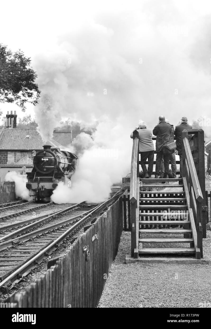 Photographers capture a smoky steam train departure from Grosmont on the North Yorkshire Moors Railway. - Stock Image