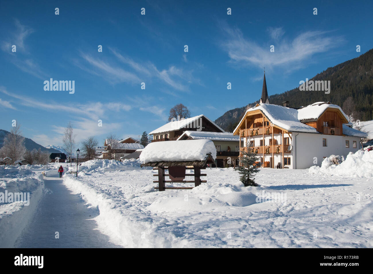 Sunny winter day. Woman walking in rural winter landscape, Weissensee, Carinthia, Austria Stock Photo