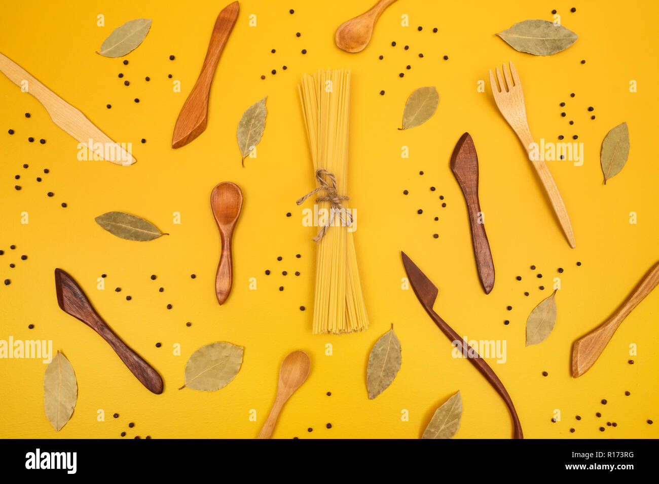 Handcrafted wooden utensils, pasta and spices. Flat lay composition on bright yellow background. - Stock Image