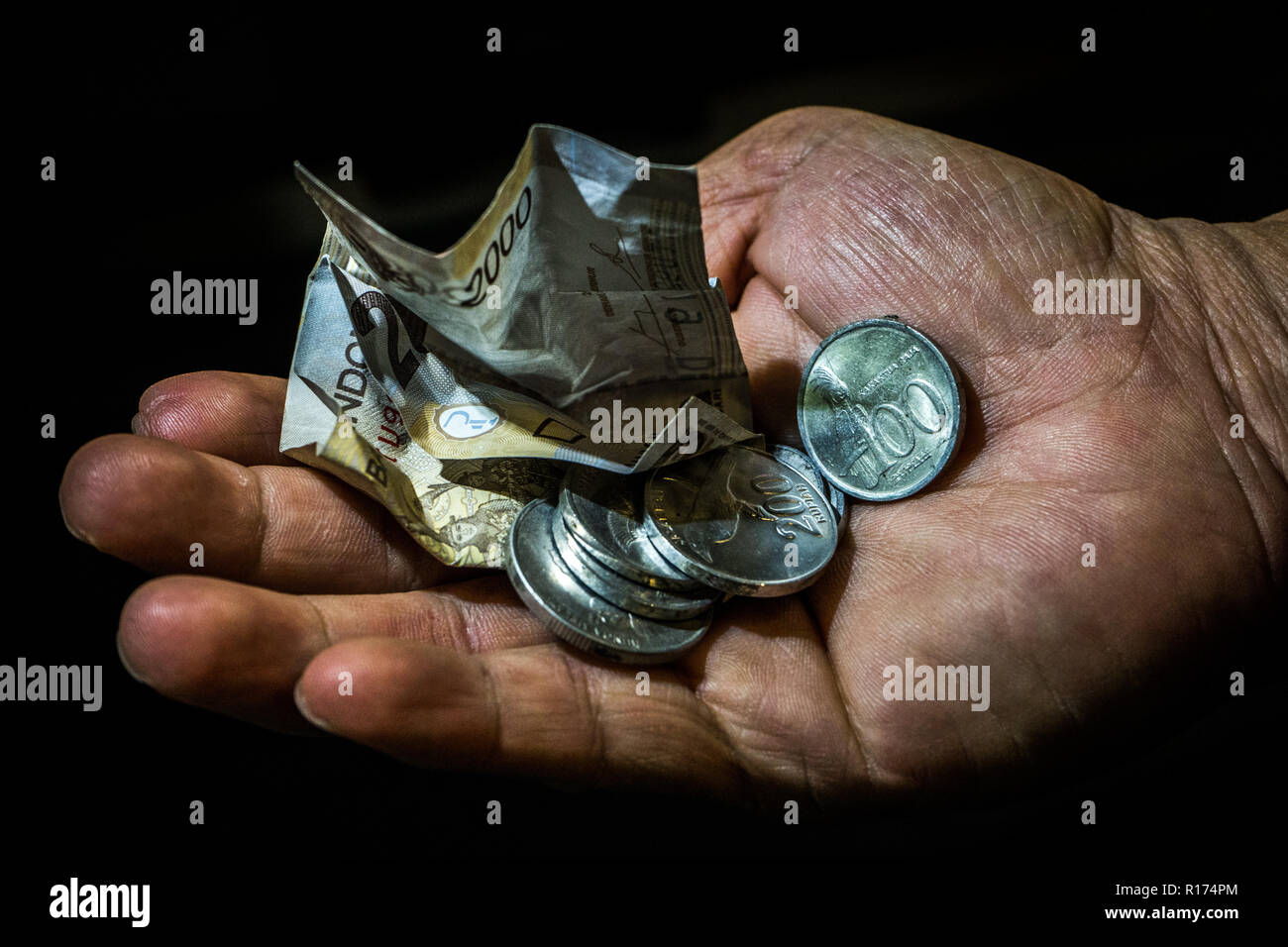 Indonesia rupiah small bill and coins in the hand of an asian person isolated. Concept of begging for leaving, poor person. Stock Photo