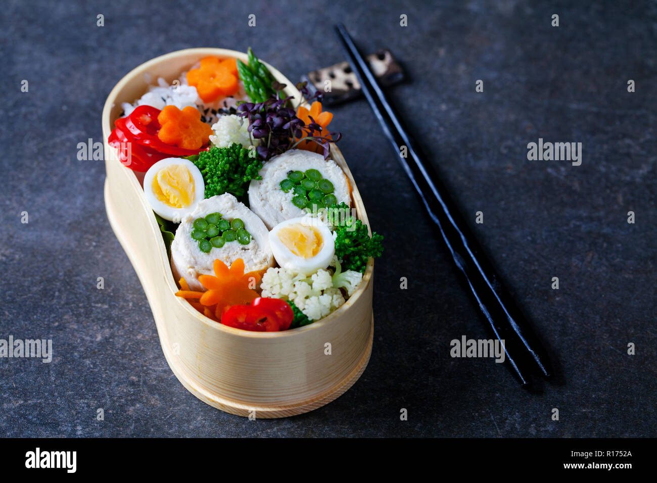 Japanese bento box with chicken stuffed with asparagus, rice, vegetables and quail eggs - Stock Image