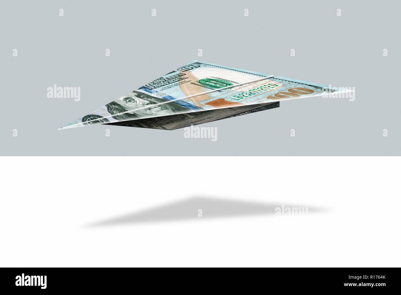 US dollar note folded into shape of plane, grey background - Stock Image