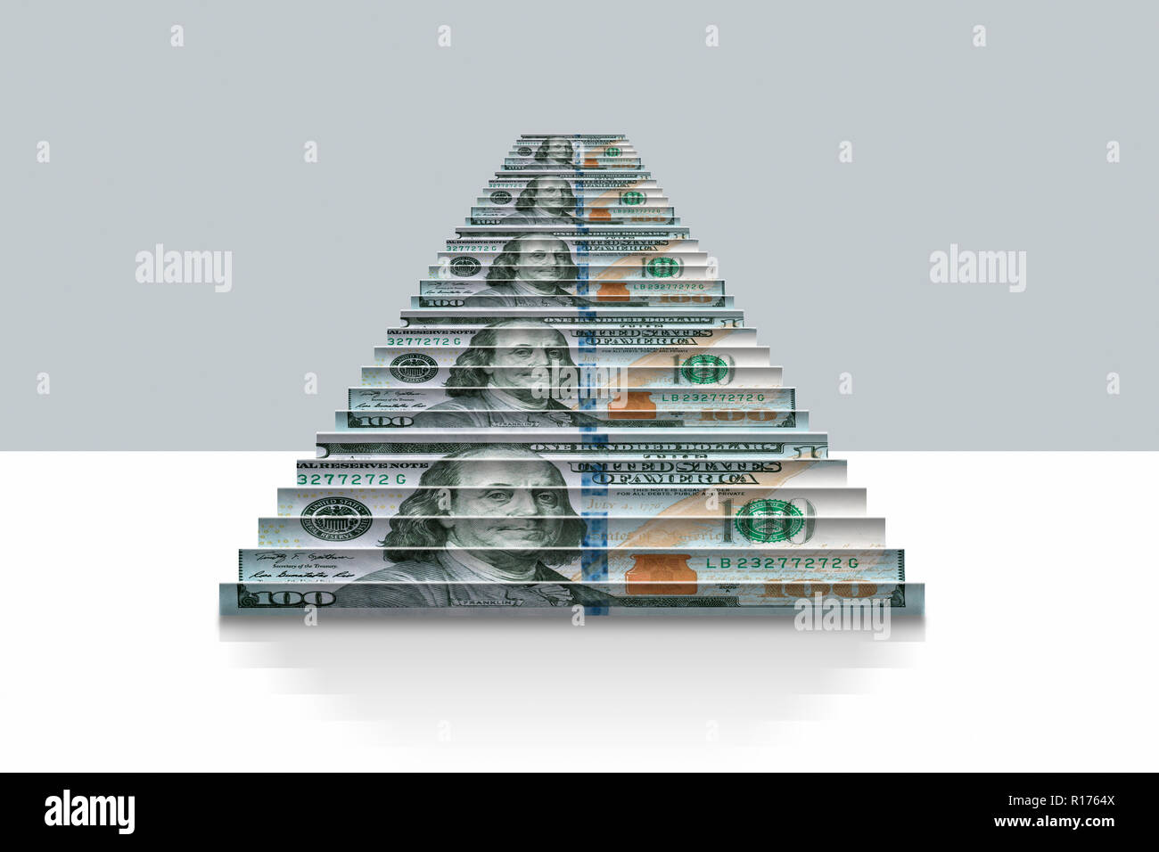 US dollar notes folded into steps, grey background - Stock Image