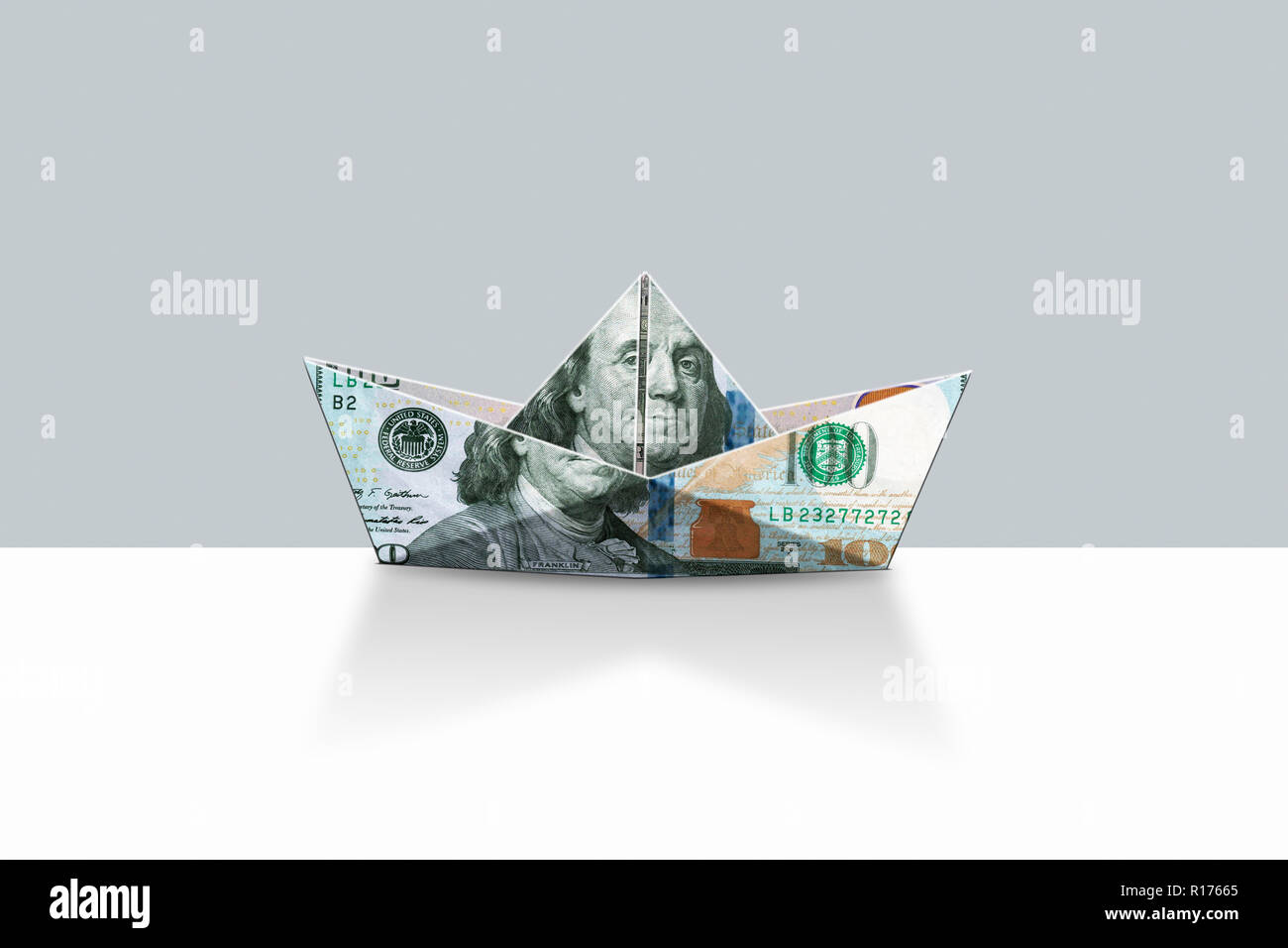 Origami shape boat made from US dollar bill, grey background - Stock Image