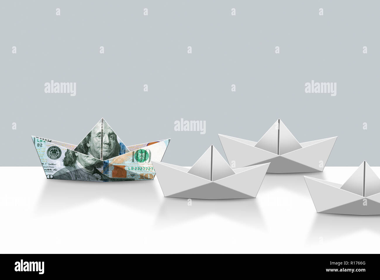US dollar note and plain paper origami boats, grey background - Stock Image