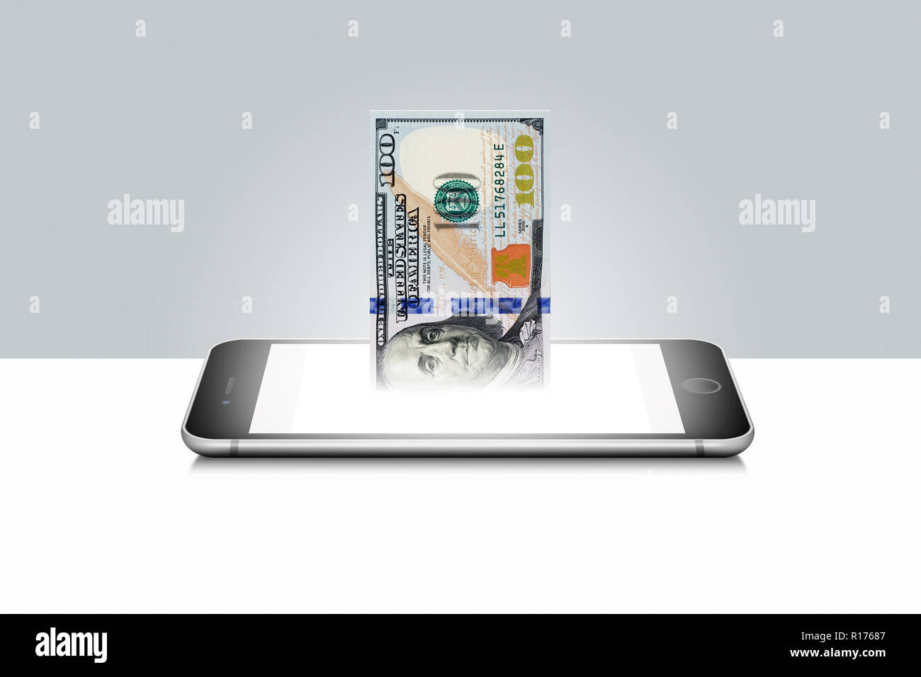 100 US dollar bill emerging from illuminated mobile phone Stock Photo