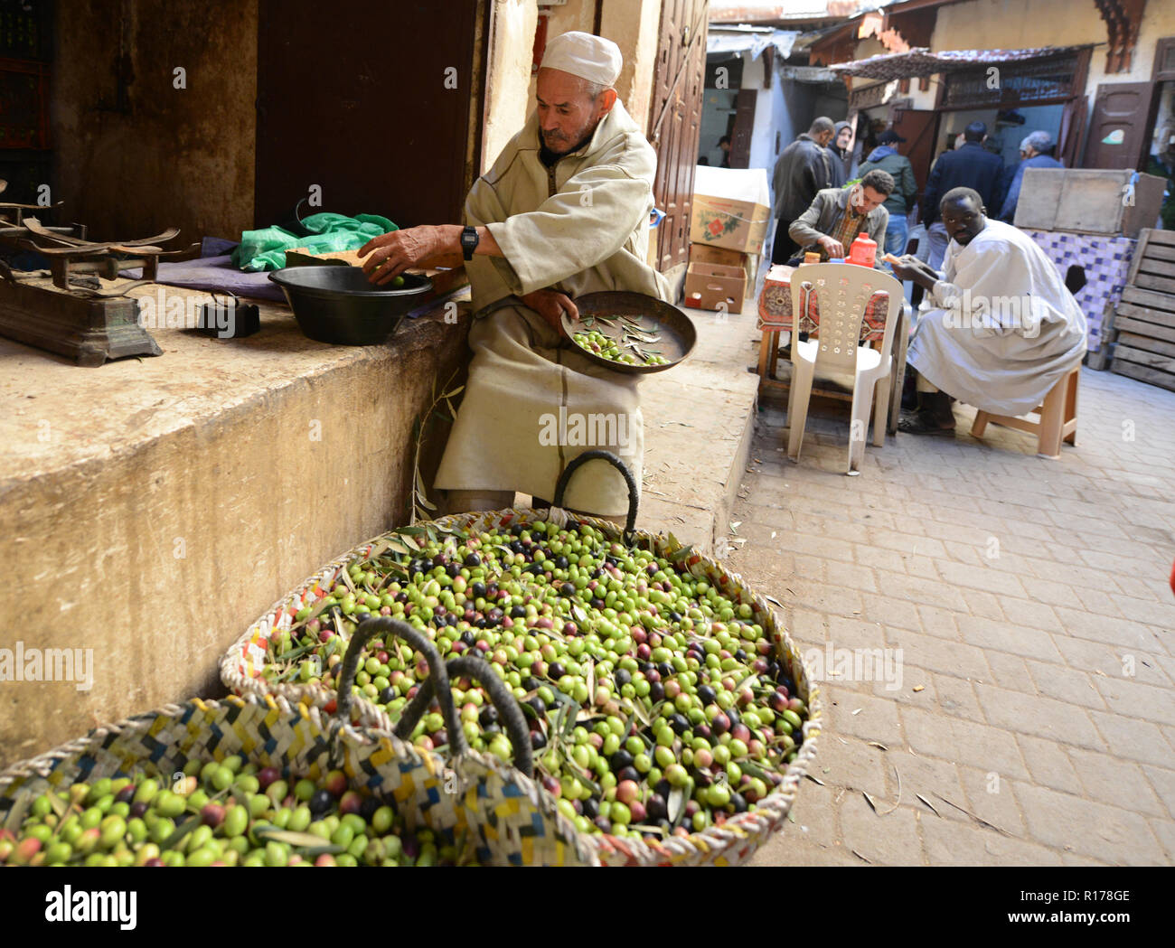 Moroccan man grading newly picked olives in the old city of Fez. - Stock Image