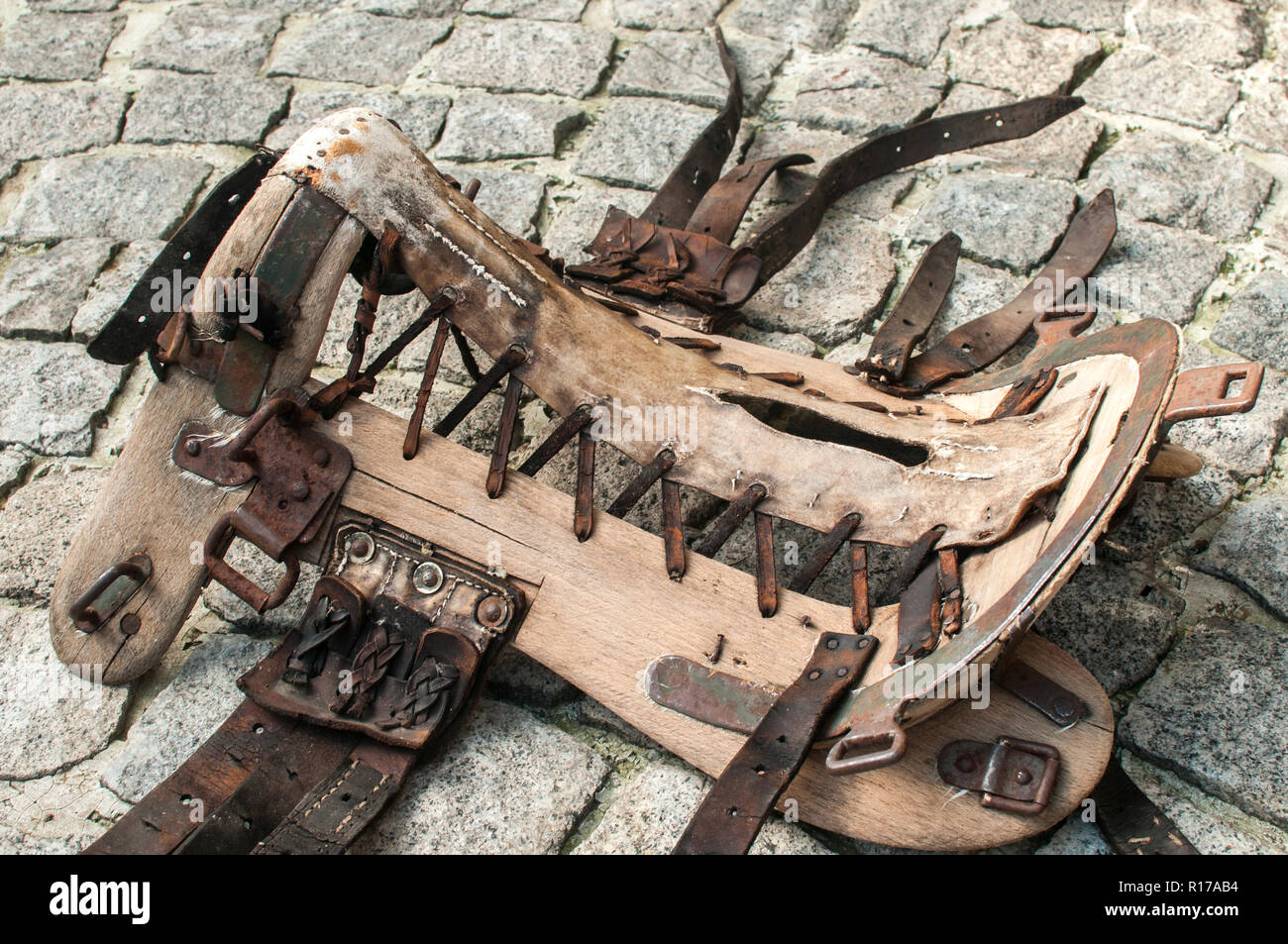 Old vintage horse saddle leather and wooden base frame tree closeup on stone paved ground surface - Stock Image
