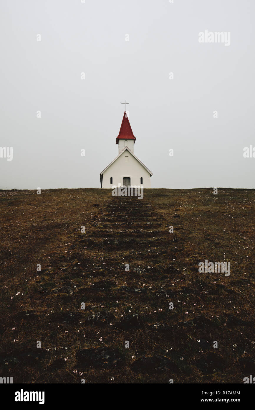 The small Breidavik Church and steps in the bleak low cloud Iceland landscape of the Westfjords. - Stock Image