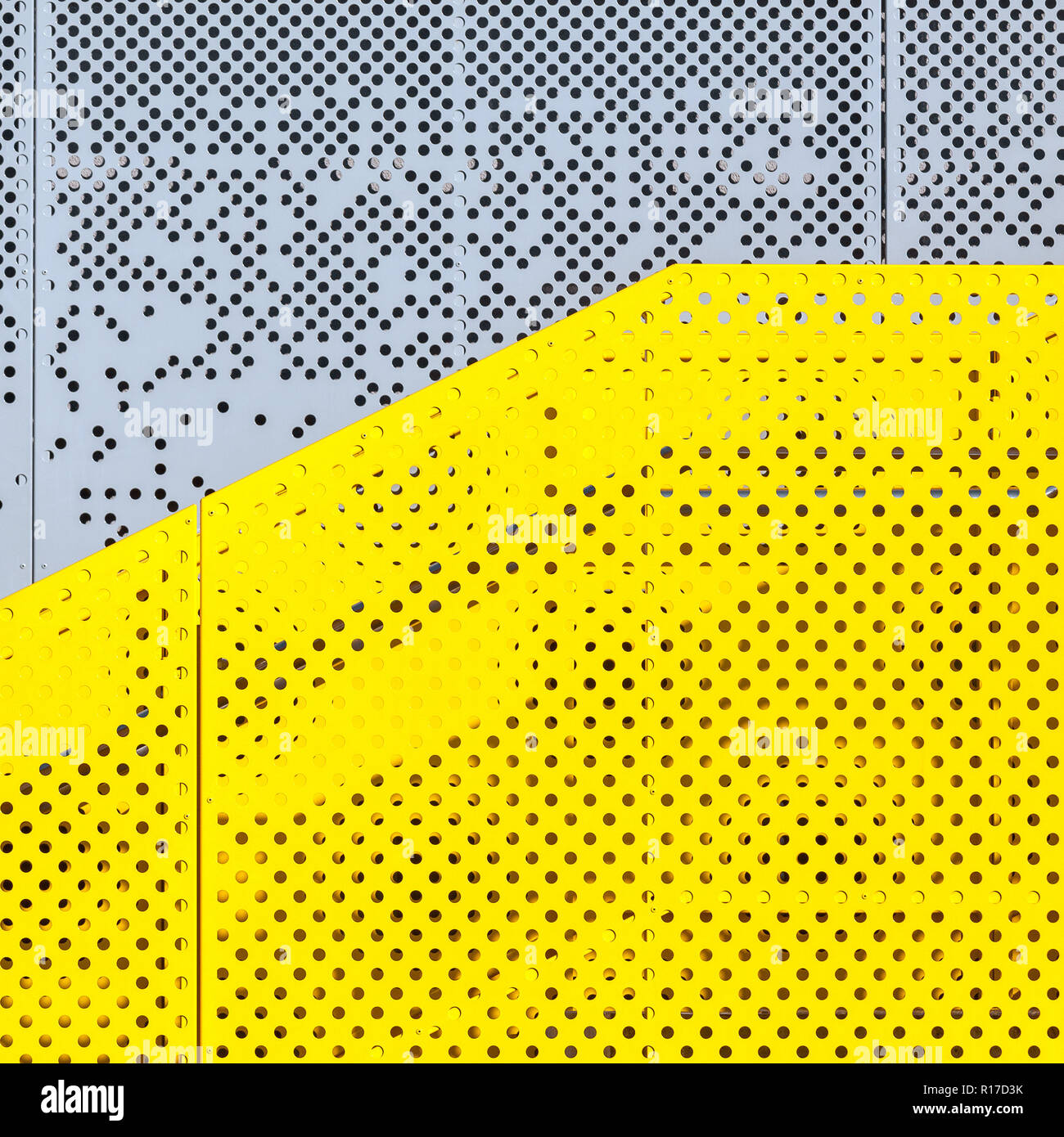 Grey and yellow perforated industrial metal background, abstract dotted texture - Stock Image