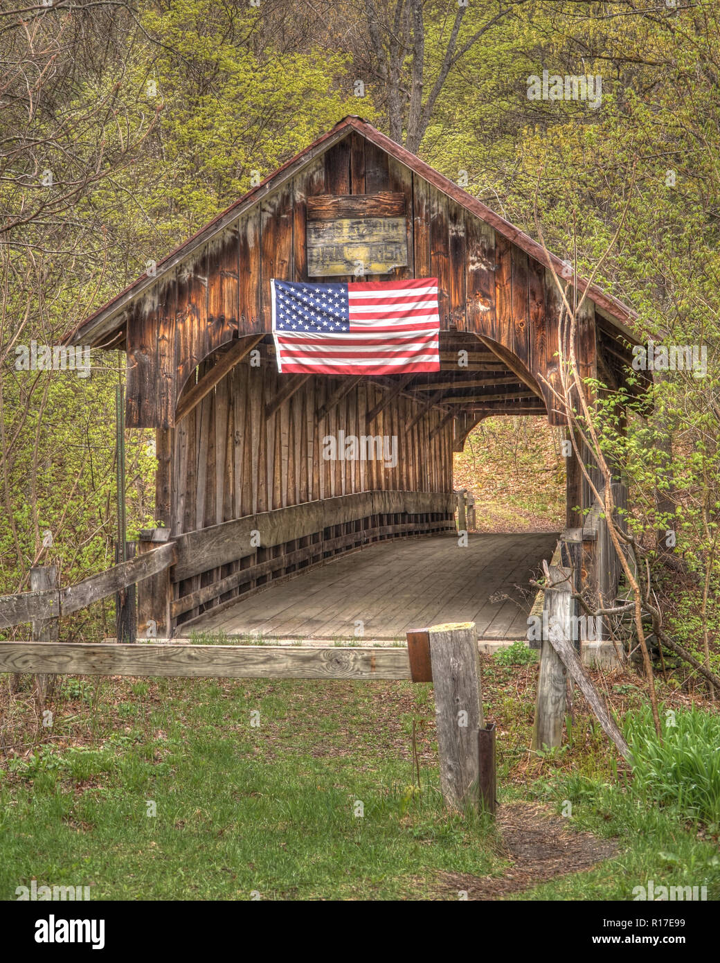 An abandoned covered bridge proudly fly's the American Flag on its weathered wood design in the early fall. - Stock Image