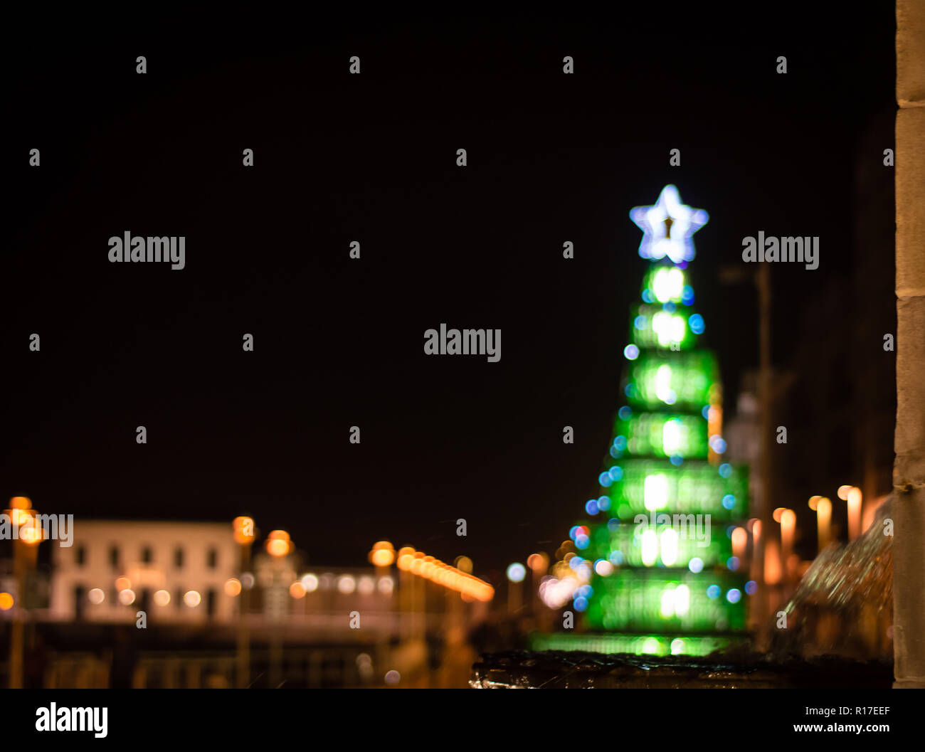 a unfocused christmas background with colorful lights on a Christmas tree, with the fountain of Pelayo on first term.Gijon, Spain, Europe - Stock Image
