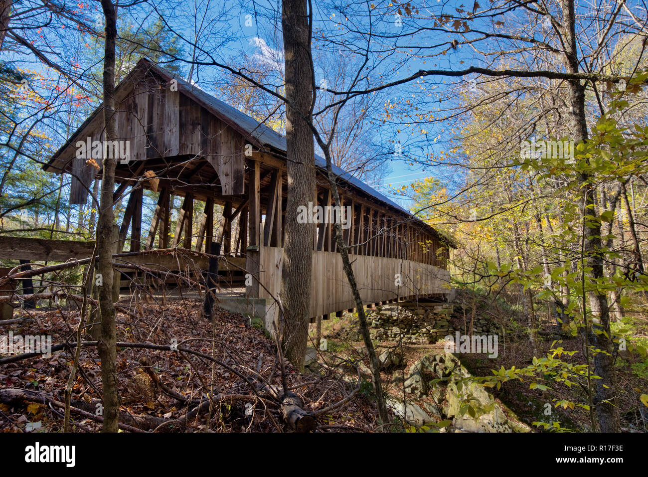 A covered bridge has been abandoned and sits in need of repair off the roadway in the countryside as it slowly falls apart over a ravine. - Stock Image